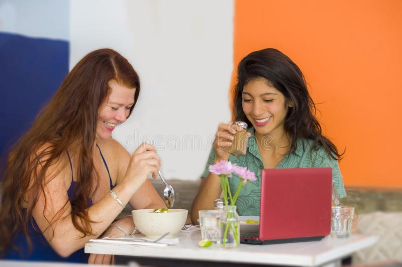 Young attractive hispanic girl sitting at modern cafe having lunch with happy woman as girlfriends meeting for discussing project stock photos