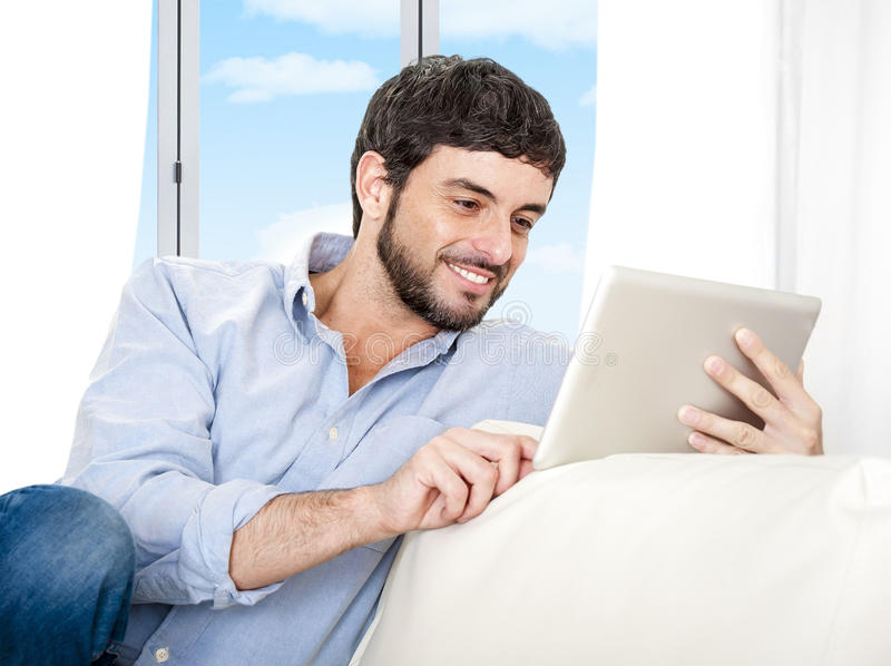 Young attractive Hispanic man at home sitting on white couch using digital tablet stock image