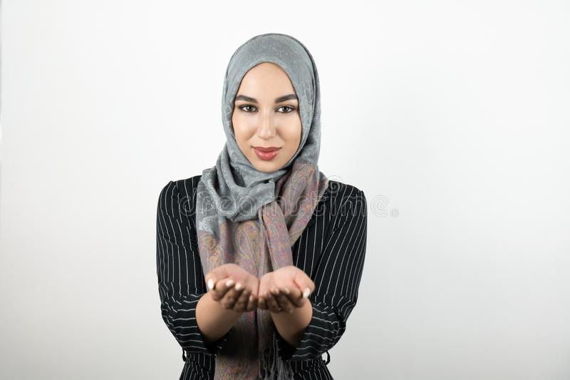 Young attractive hopeful Muslim woman wearing turban hijab, headscarf holding her hands together isolated white royalty free stock photos
