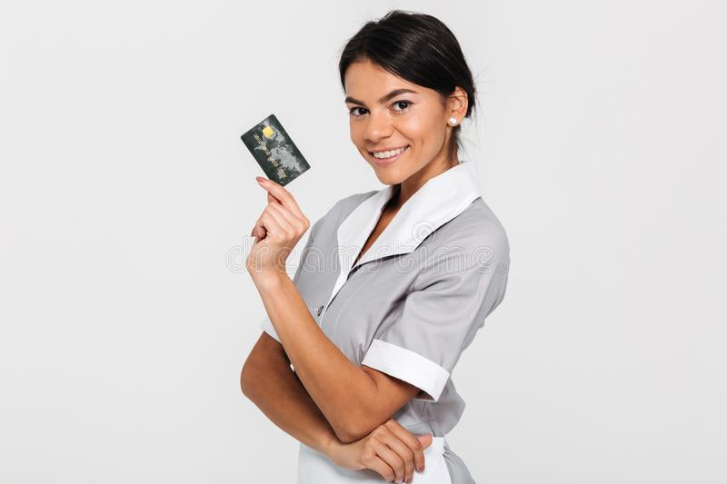 Young attractive housekeeper in gray uniform holding credit card. And looking at camera, isolated on white background stock photo