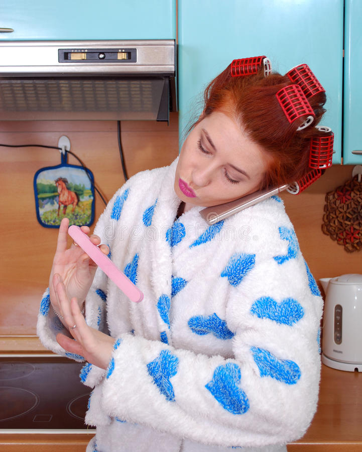 The young attractive housewife in kitchen in hair curlers speaks by phone and does manicure. Stands near a plate in a dressing gown stock image