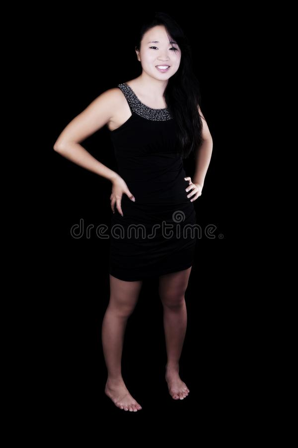 Young Attractive Japanese American Woman In Black Dress. Attractive Japanese American Woman Standing In Black Dress On Dark Background Smiling stock image