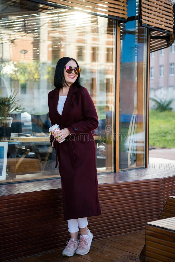 Young attractive lady in marsala coat drink coffee to go. Smiling beautiful hipster happy woman in city street, wearing royalty free stock images