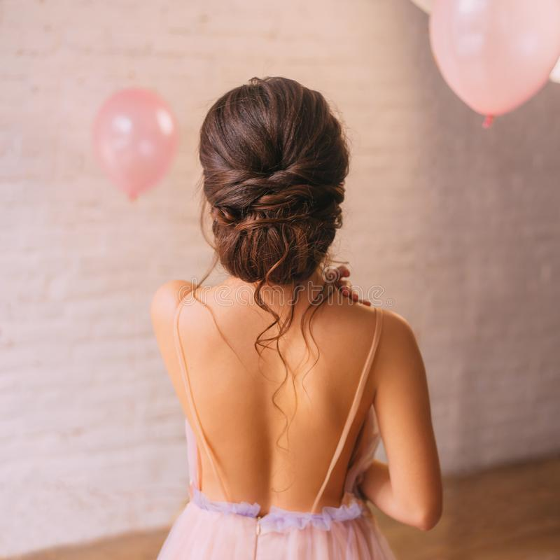 A young attractive lady, a peach dress with a purple color, shows a bare open back and a great neat dark hair hairstyle royalty free stock image