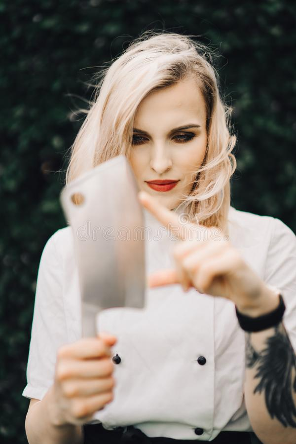 Young attractive lady, sous-chef is standing with the knife. stock images