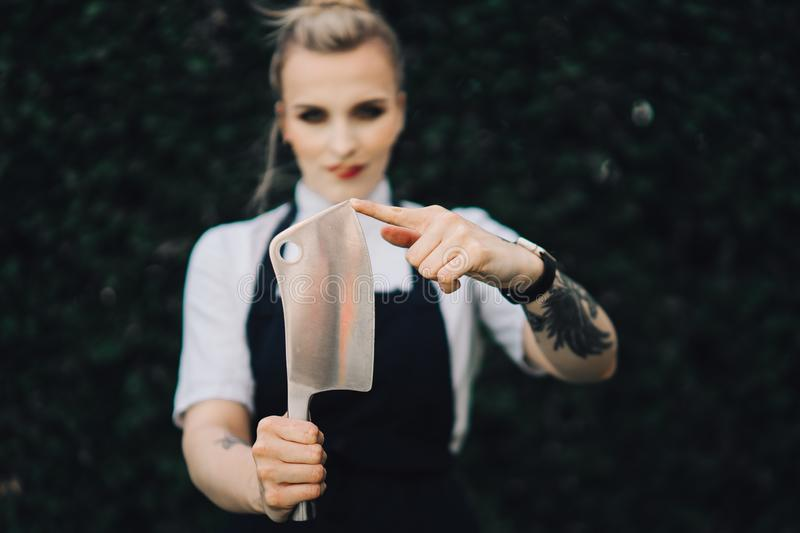 Young attractive lady, sous-chef is standing with the knife. Young attractive lady, professional cook is smiling. Tattooed with makeup, knife and kitchen royalty free stock images