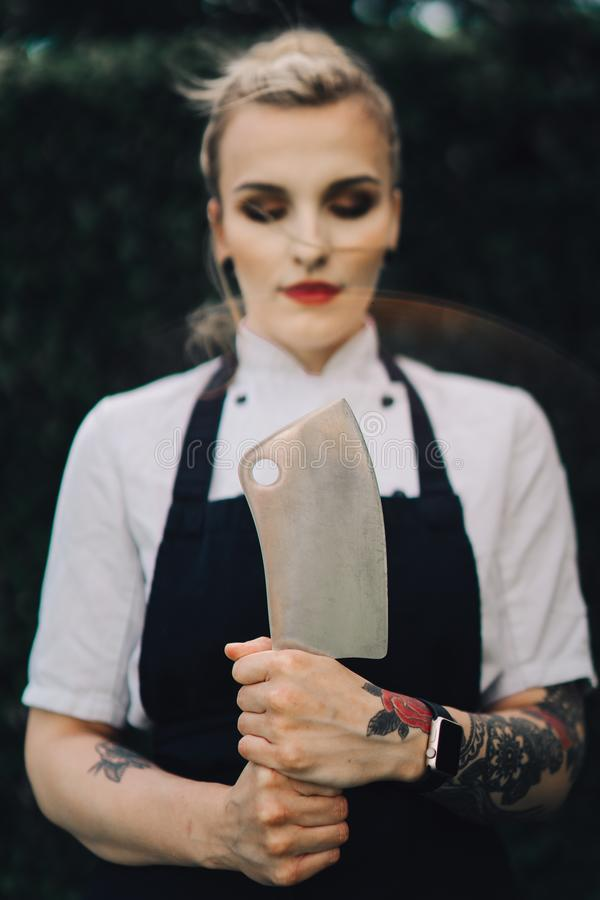 Young attractive lady, sous-chef is standing with the knife. Young attractive lady, professional cook is smiling. Tattooed with makeup, knife and kitchen stock photo