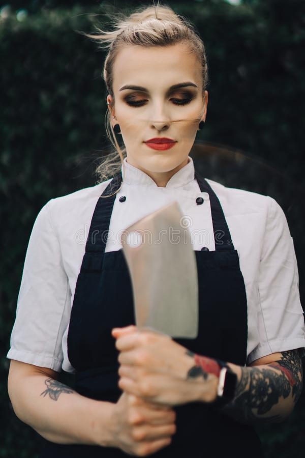 Young attractive lady, sous-chef is standing with the knife. Young attractive lady, professional cook is smiling. Tattooed with makeup, knife and kitchen royalty free stock photos