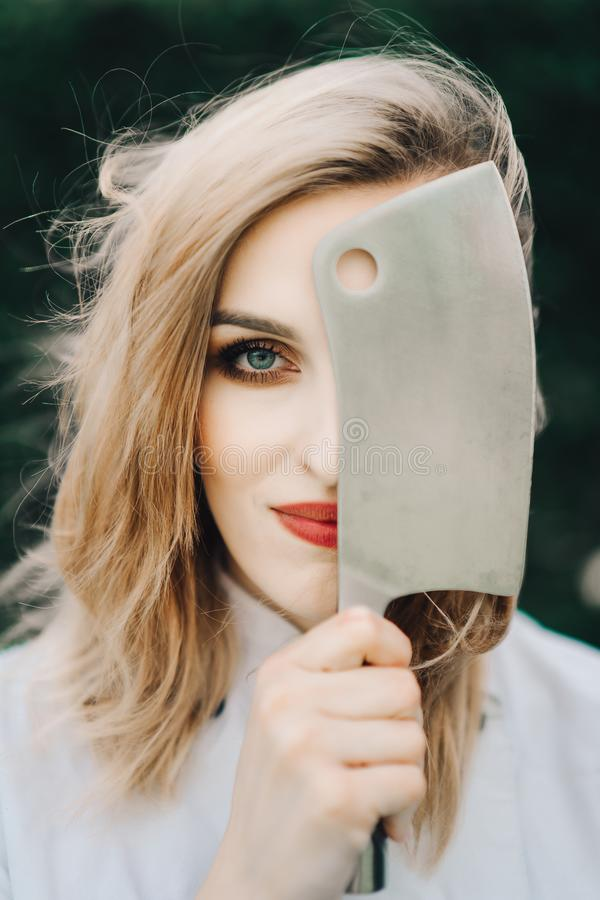 Young attractive lady, sous-chef with knife. Young attractive lady, professional cook is smiling. Half face is covered with big knife, tattooed, blue eyed, with royalty free stock photography