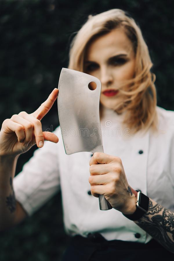 Young attractive lady, sous-chef is standing with the knife. Young attractive lady, professional cook is smiling. Tattooed, blue eyed, with makeup, knife and stock photography