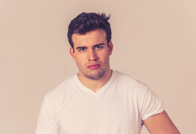 Young attractive latin man with angry facial expression. Close up portrait of an attractive young man with angry face looking furious and mad Isolated on neutral royalty free stock image
