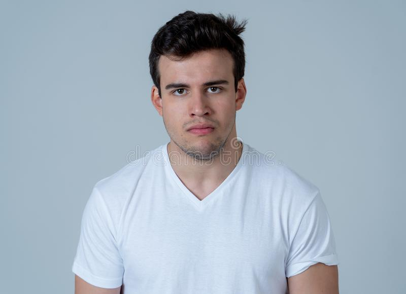 Young attractive latin man with angry facial expression. Close up portrait of an attractive young man with angry face looking furious and mad Isolated on neutral stock image