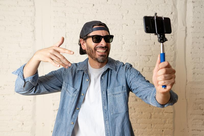 Young attractive latin man taking a selfie with his smart cell phone. royalty free stock photo