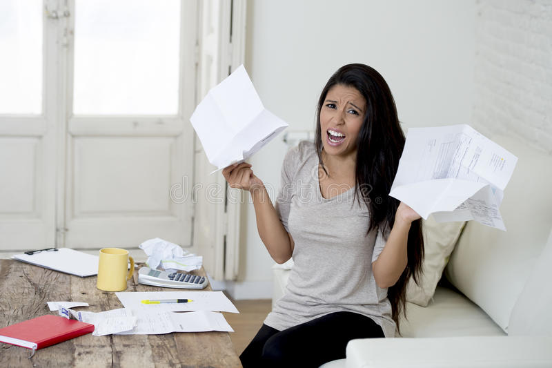 Young attractive latin woman at home living room couch calculating monthly expenses worried in stress. Crazy desperate latin woman at home living room couch royalty free stock photos