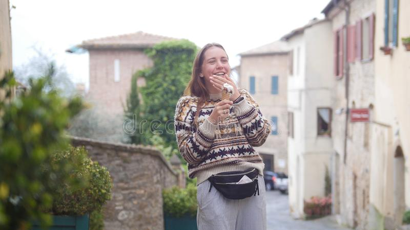 Young attractive laughing woman eat icecream on the street of the historic town stock photography