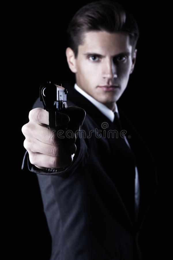 Young attractive macho in suit with gun royalty free stock images