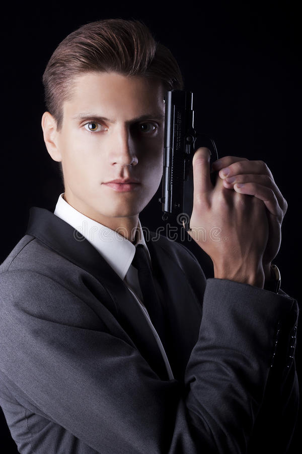 Young attractive macho in suit with gun stock image