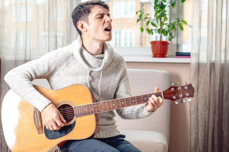Young attractive male musician sitting on a chair playing acoustic guitar in room. Concept of music as a hobby stock image