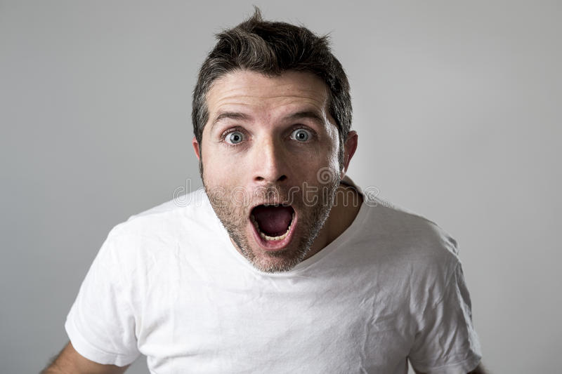 Young attractive man astonished amazed in shock surprise face expression and shock emotion. Young attractive man astonished and amazed in shock and surprise face stock photo