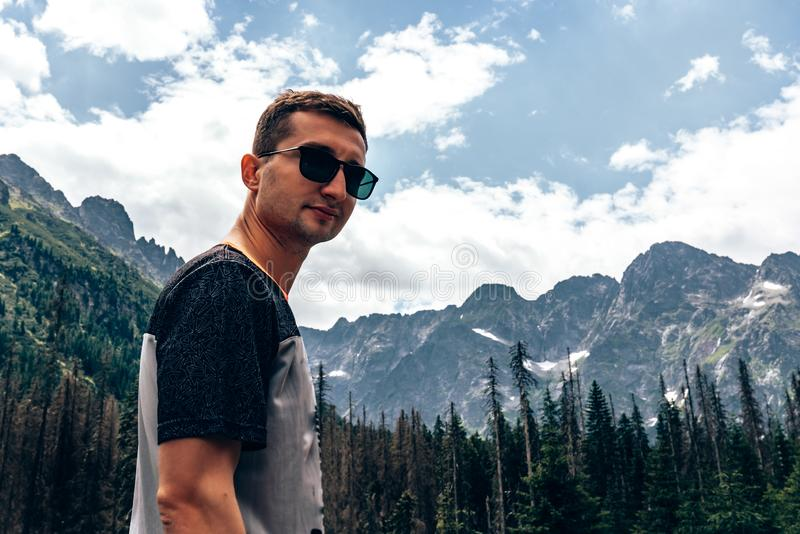 Young attractive man in black sunglasses and casual t-shirt looking at the camera, beautiful mountainss on the stock photography