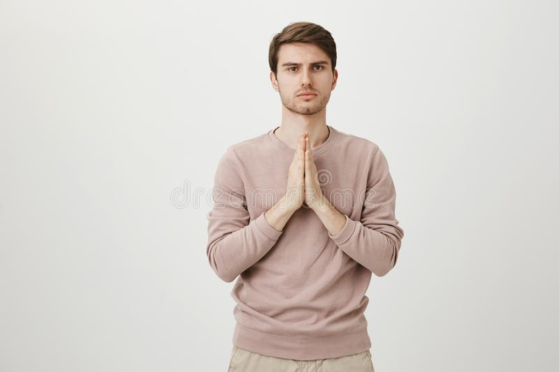 Young and attractive man with bristle standing with praying or begging gesture while expressing confidence and being. Calm, over gray background. Yoga trainer royalty free stock images