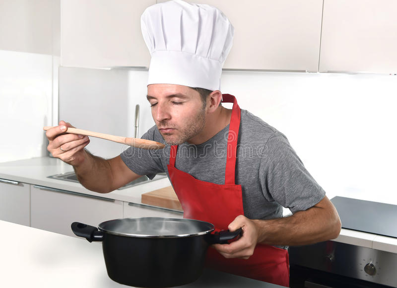 Young attractive man in chef hat and red cook apron testing flavor royalty free stock images