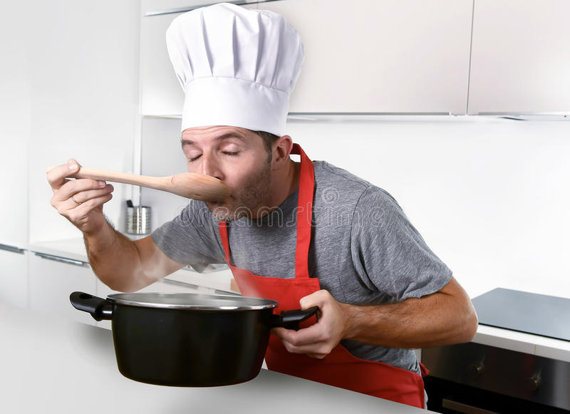 Young attractive man in chef hat and red cook apron testing flavor. While cooking soup holding pot with steam at modern home kitchen royalty free stock image