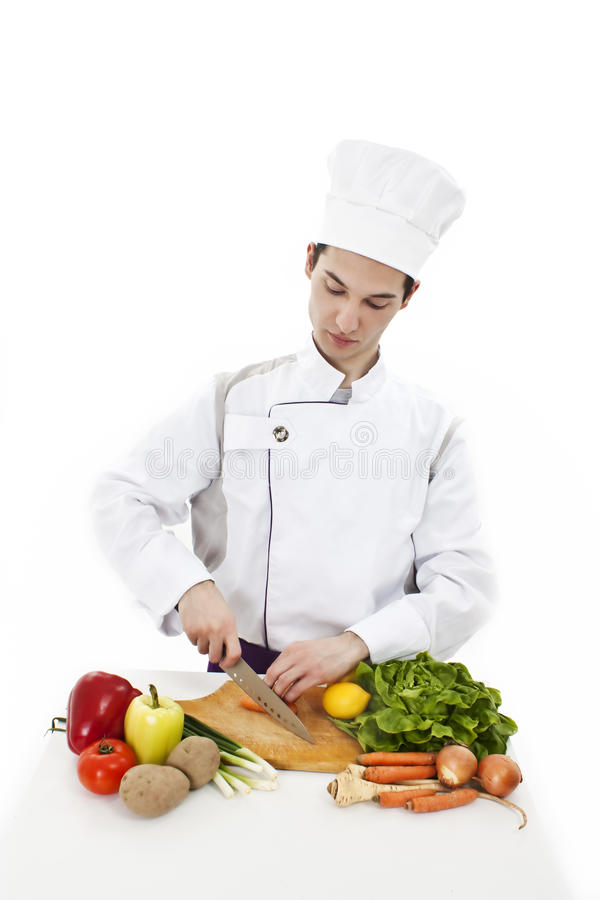 Young attractive man, chef preparing food stock photos