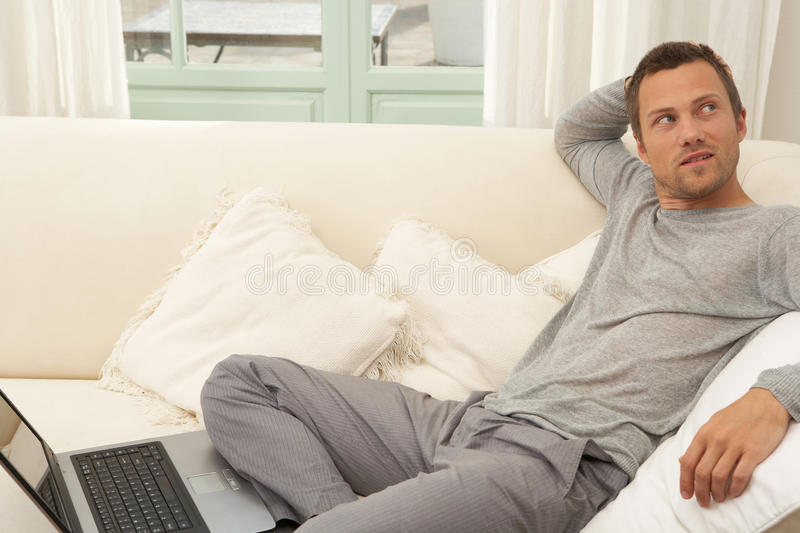 Download Young Attractive Man On Couch With Laptop At Home. Stock Photo - Image: 29314808