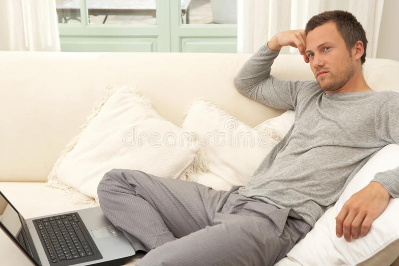 Download Young Attractive Man On Couch With Laptop At Home. Stock Image - Image: 29314833