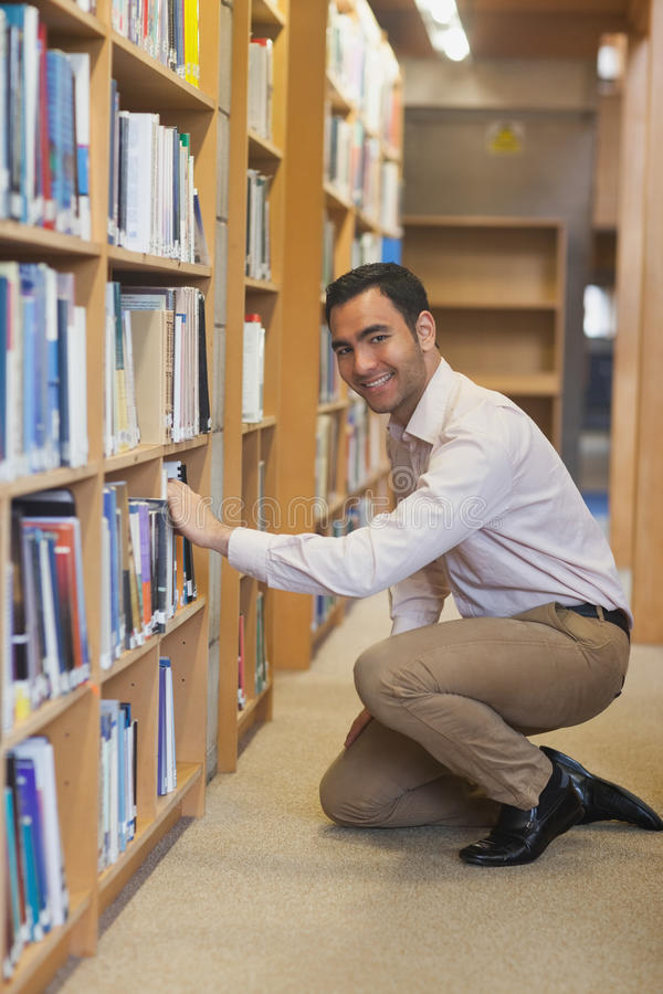 Young attractive man cowering in front of bookshelves. Smiling friendly at camera royalty free stock image