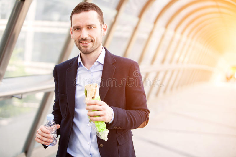 Young attractive man eating fast his lunch royalty free stock image