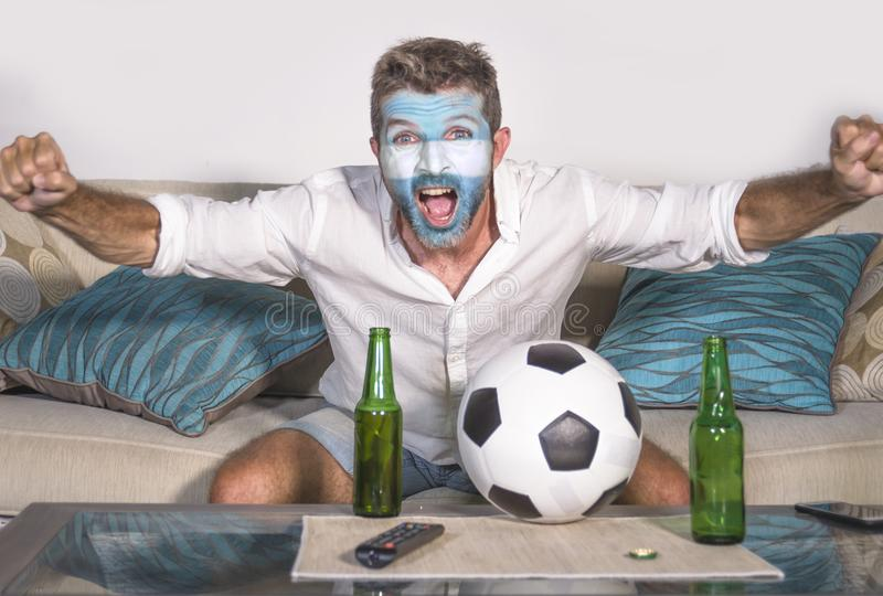 Young attractive man football supporter with Argentina flag painted face happy and excited watching cup match on TV celebrating vi stock image