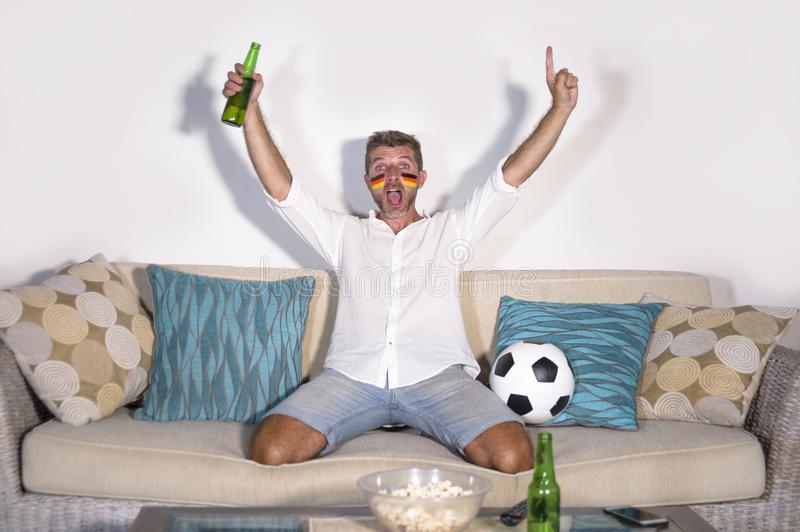 Young attractive man football supporter with Germany flag painted face happy and excited watching cup match on TV celebrating vict stock photo