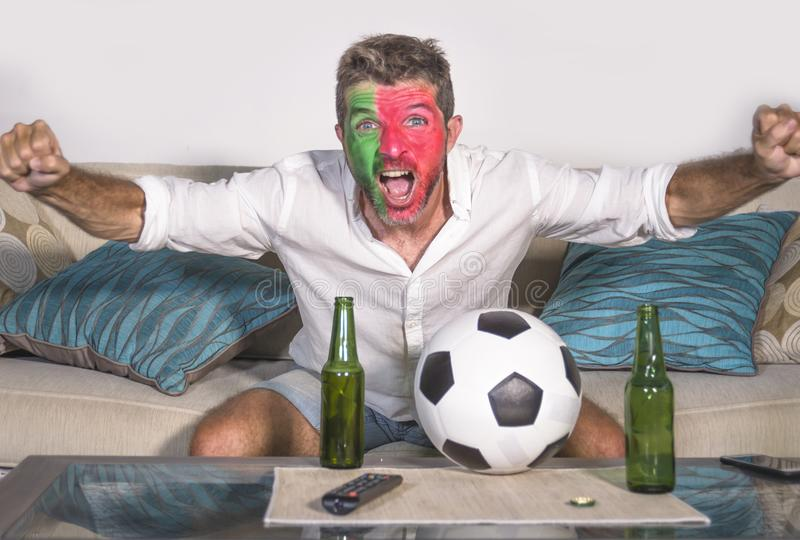 Young attractive man football supporter with Portugal flag painted face happy and excited watching cup match on TV celebrating vic royalty free stock image