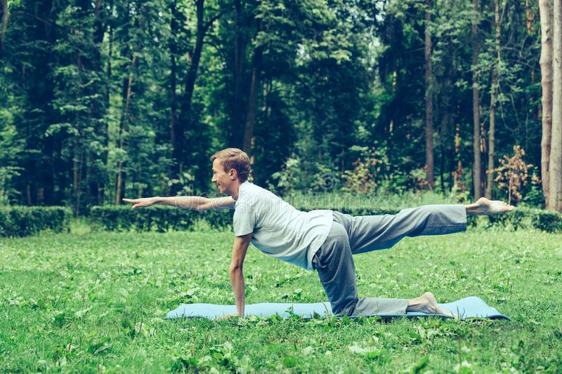 Young attractive man in a gray T-shirt and sweatpants doing yoga pose in the park. Keeps balance stock images