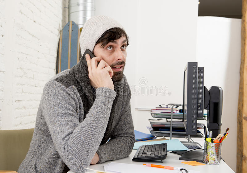 Young attractive man in hipster beanie and trendy style businessman working in stress. At home office with desktop computer as creative designer talking on royalty free stock photos