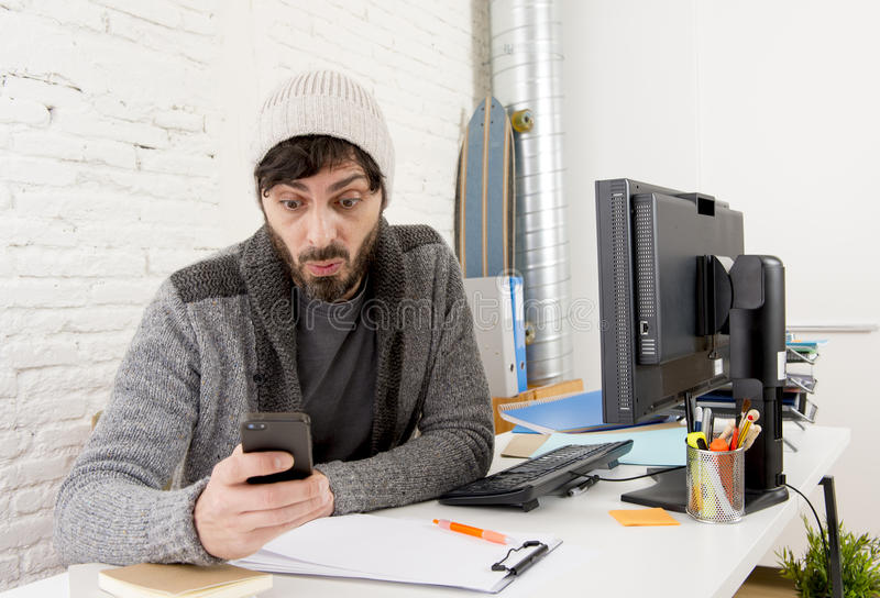 Young attractive man in hipster beanie and trendy style businessman working in stress. At home office with desktop computer as creative designer using internet stock photos