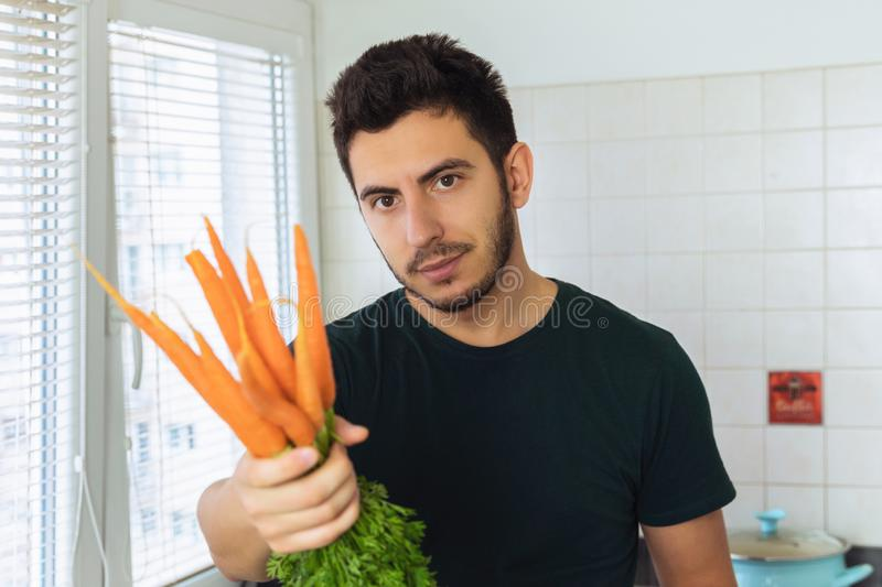 A young attractive man holds in his hands a fresh organic carrot. Offers her taste royalty free stock photos