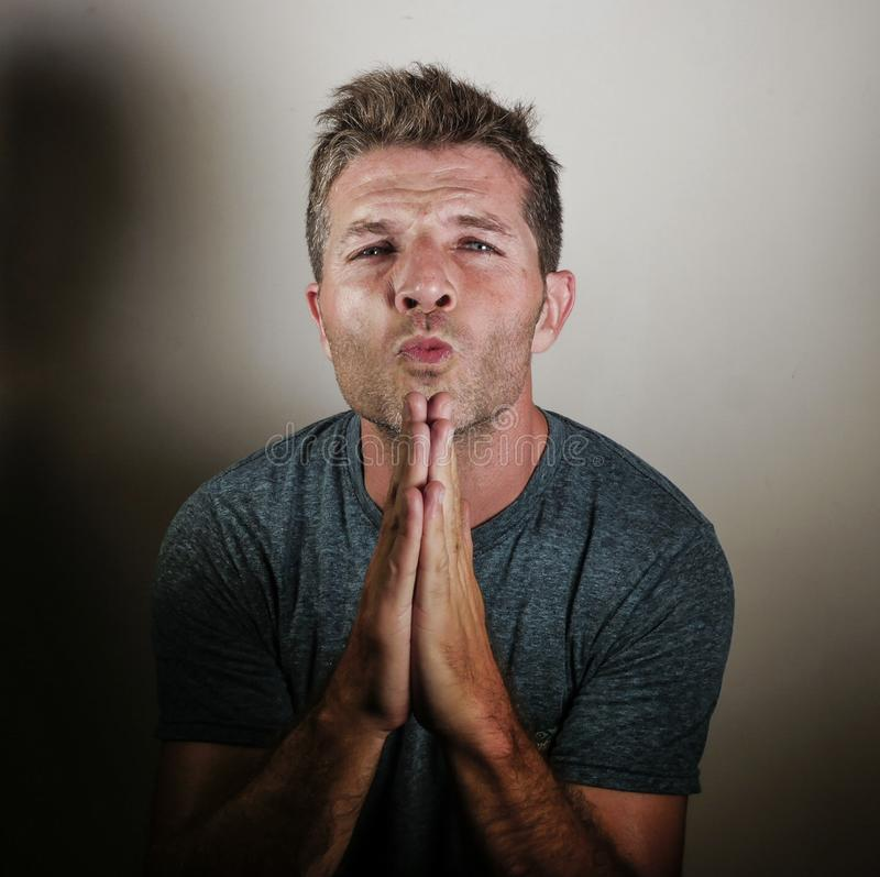 Young attractive man looking anxious with hands on his mouth imploring begging and praying as if hoping and wishing something feel stock images