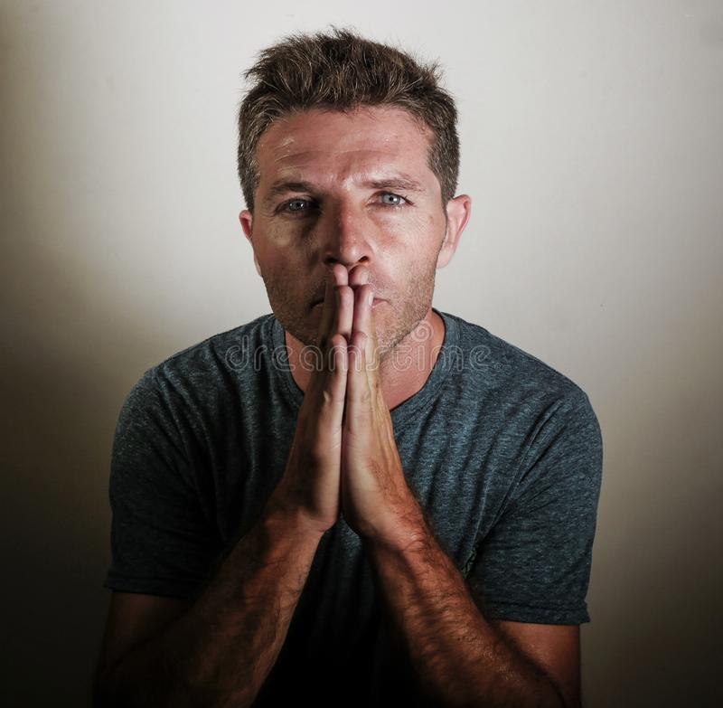 Young attractive man looking anxious with hands on his mouth imploring begging and praying as if hoping and wishing something feel. Ing stressed on isolated stock image