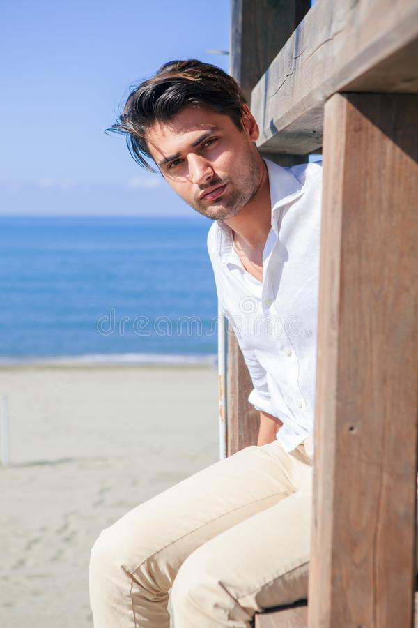 Man with white shirt on beach vacation looking out. stock image