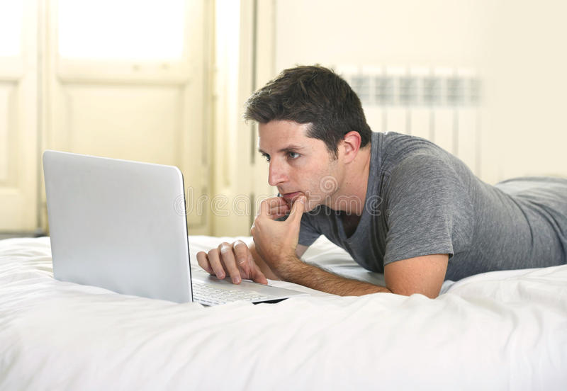 Young attractive man lying on bed or couch working on computer laptop typing connected to internet. In technology and modern lifestyle concept royalty free stock photography