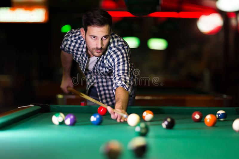 Young attractive man playing pool in bar. Alone stock image