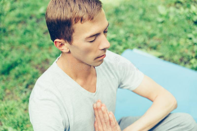A young attractive man practices yoga in nature and meditates with his eyes closed in the lotus position stock photos