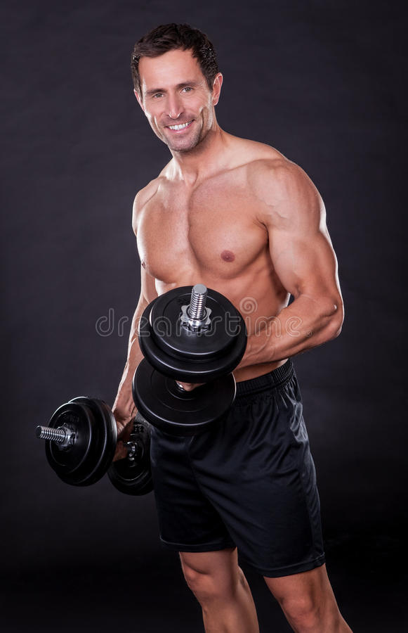Young Attractive Man Pumping Weights royalty free stock photography