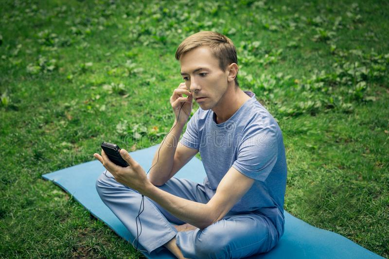 A young attractive man puts on headphones and listens to music in the park stock image