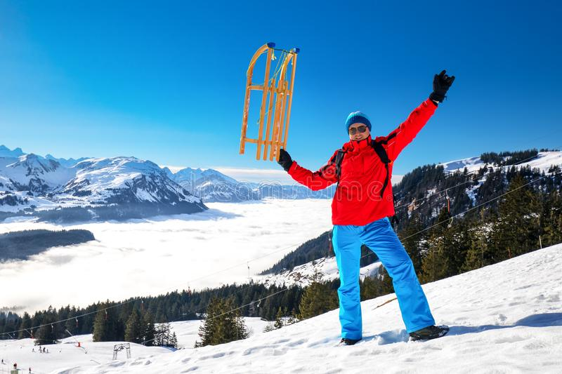 Young attractive man ready to go sledding in Swiss Alps during winter vacation stock photo