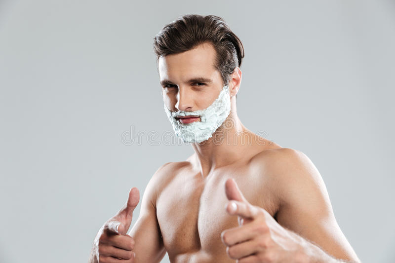 Young attractive man with shaving foam on face pointing. Picture of young attractive man standing isolated over grey background with shaving foam on face and stock photos