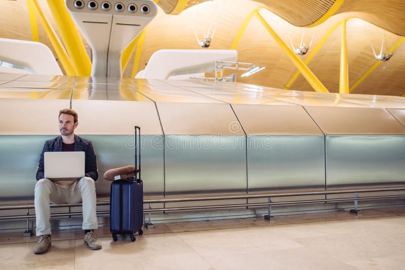 Young attractive man sitting at the airport working with a laptop waiting his flight with a suitcase stock photos